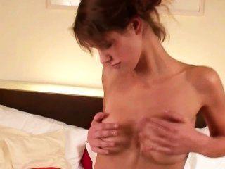 Morena adolescente bronzeado usando um brinquedo na cama