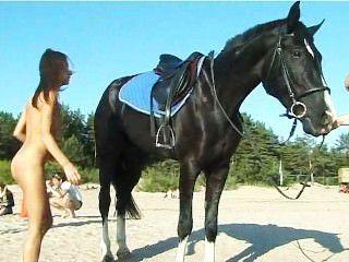 Adolescente nu andando de cavalo na praia vira cabeças