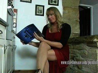 A dona de casa quente dangles seus stilettos e teases seus pés de nylon puros