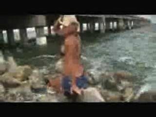 Modelo de menina bonita muscular flexionando e posando sobre as praias.wmv
