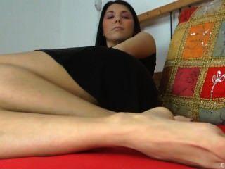 Menina lê uma revista e teases com pés