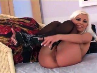 Bela garota de glamour loira brinca e se masturba em lingerie e calcanhares