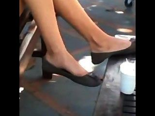 Pés adolescentes e pernas calçados shoeplay dangling flats