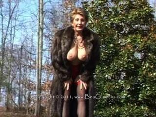 Senhora em um casaco de pele que masturbating ao ar livre.
