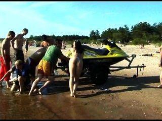 Este adolescente nudista tiras nuas em uma praia pública