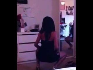 Latina menina quente em vestido apertado agitando-o na frente do espelho